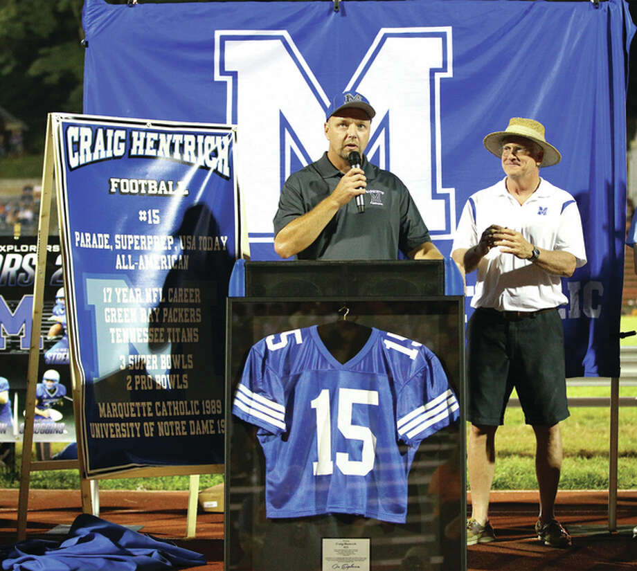 Former Marquette Catholic star Craig Hentrich, who went on to play college football at Notre Dame before a long career as a punter in the NFL, addresses the crowd during a ceremony retiring his jersey No. 15 on Saturday nightat Public School Stadium in Alton. At right is Marquette principal Mike Slaughter. Photo: Billy Hurst / For The Telegraph