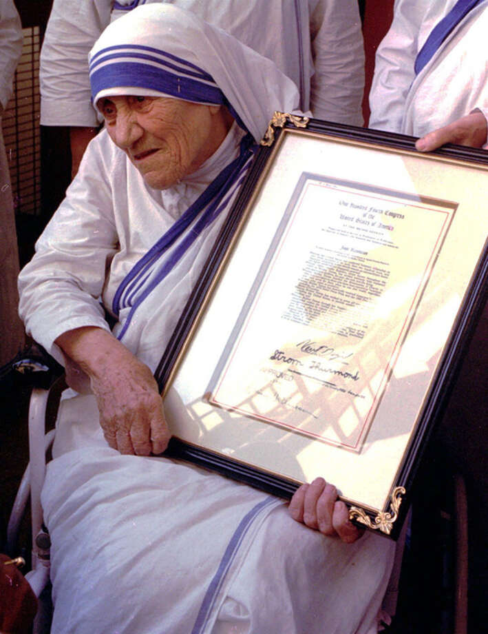 "In this Nov. 16, 1996, file photo, Mother Teresa holds the resolutions of honorary American citizenship after they were presented to her by American Ambassador to India Frank G. Wisner at the Missionaries of Charity in KolKata, formerly known as Calcutta, India. With Sunday, Sept. 4, marking the canonization of Mother Teresa, Pope Francis honored the nun who cared for the ""poorest of the poor"" as the epitome of his call for mercy. Photo: (AP Photo, File)"