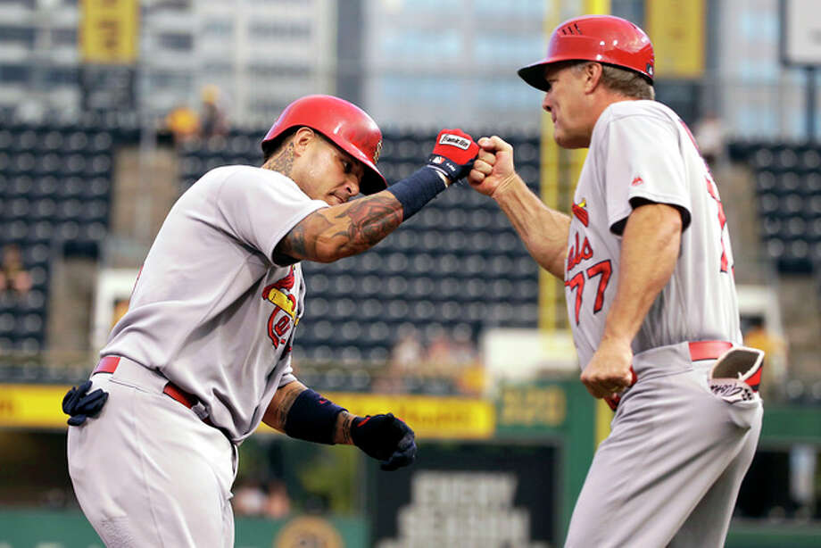 St. Louis Cardinals' Yadier Molina, left, rounds third to greetings from coach Chris Maloney (77) after hitting a grand slam off Pittsburgh Pirates starting pitcher Ryan Vogelsong during the first inning of a baseball game in Pittsburgh, Tuesday, Sept. 6, 2016. (AP Photo/Gene J. Puskar) Photo: AP