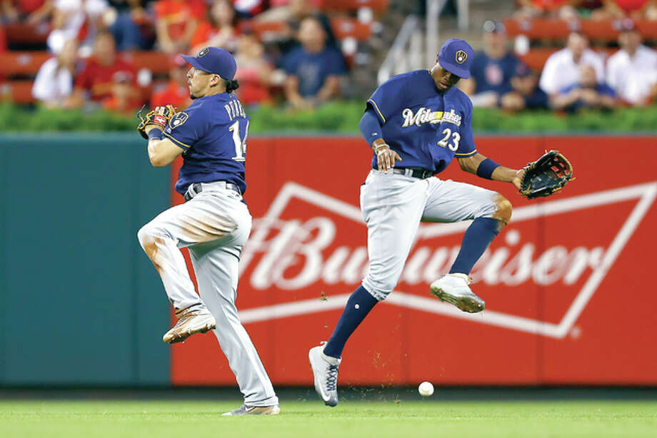 Brewers second baseman Hernan Perez, left, and center fielder Keon Broxton cannot come up with a ball hit by the Cardinals' Jedd Gyorko in the third inning Thursday night in St. Louis. Perez was charged with an error on the play and Gyorko reached second base. Photo: Billy Hurst | Associated Press