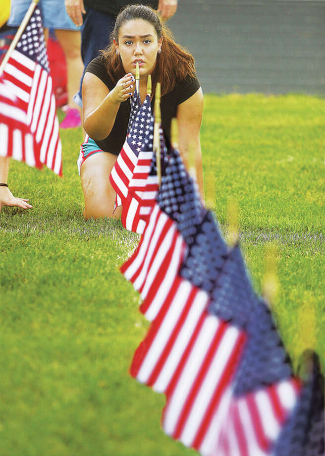 Civic Memorial High School junior Daniela Rodriguez guides other students as they set up the rows and rows of American flags on the high school football field in Bethalto Thursday morning for a September 11th Civic Memorial High School Remembers 9/11 ceremony Thursday evening. The students placed perfectly even rows of 2,996 flags, one for each person who died 15 years ago in the 2001 terrorist attacks on New York, Washington D.C. and United Flight 93, which crashed in a field near Shanksville, Pennsylvania. Most of the students were just babies at the time of the attack. The ceremony was started three years ago by physical education teacher Angela Parish after she was challenged by another teacher she met to do something in remembrance of the attacks. Photo: John Badman|The Telegraph
