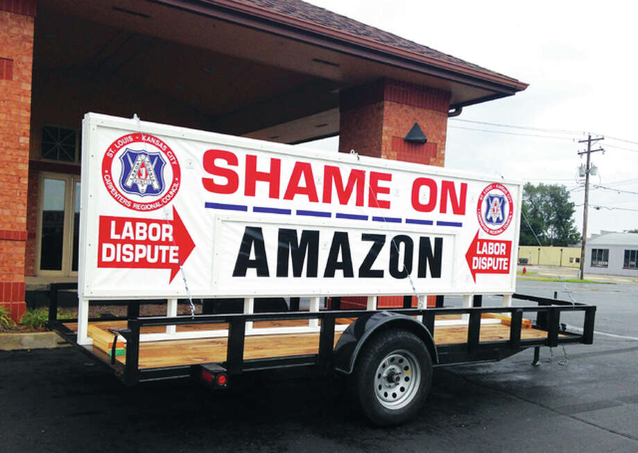 "A sign reading ""Shame on Amazon"" sits in front of the Wood River Carpenters Local. The sign is being driven around on a trailer by the St. Louis-Kansas City Carpenters Regional Council, who are protesting what they say is Amazon's use of non-local labor for their warehouse projects. Photo: Linda Weller 