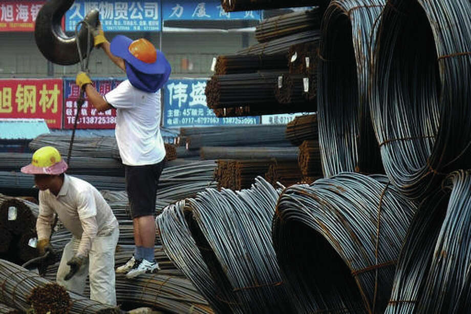 In this Aug. 1, 2016 photo, workers load steel bars at a steel market in Yichang in central China's Hubei province. China agreed to steps toward reducing its politically volatile steel exports but avoided binding commitments, as leaders of major economies ended a summit with a crowded agenda that also included trade, the Koreas and Syria.(Chinatopix via AP)