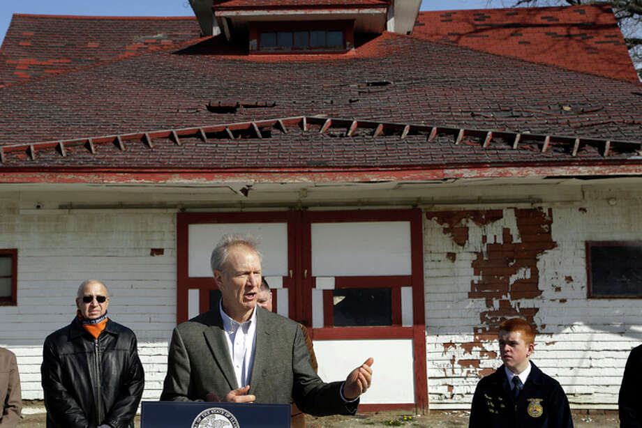 In this March 22 file photo, Illinois Gov. Bruce Rauner speaks to reporters in front of one of many barns in need of repair on the Illinois State Fairgrounds in Springfield, Illinois. With Illinois facing about $180 million in maintenance and repairs to its state fairgrounds, the organization newly formed to raise money for that work has its hands full.