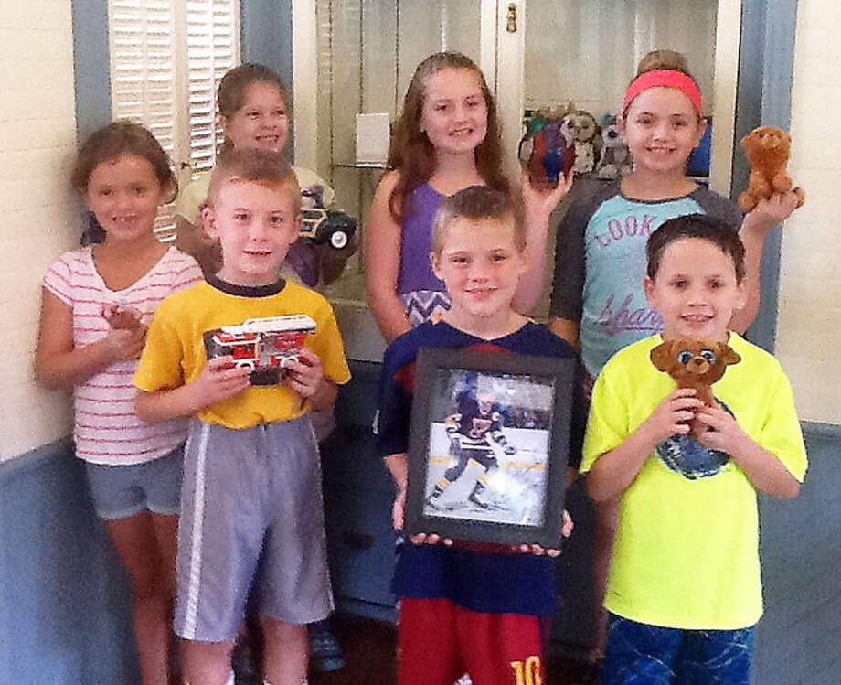 Children who participated in the first Kids' Corner collection display program at Lucy Haskell Playhouse, with the showcase in the rear. The children are holding an object from their collections: Girls: Leah O'Neill, 7; Lucy Cassenti, 8; Addie Sandifer, 9; Lauren O'Neill, 11; Boys: Josh Cordes, 6, Jake Campbell, 7; and Johnny O'Neill, 8.