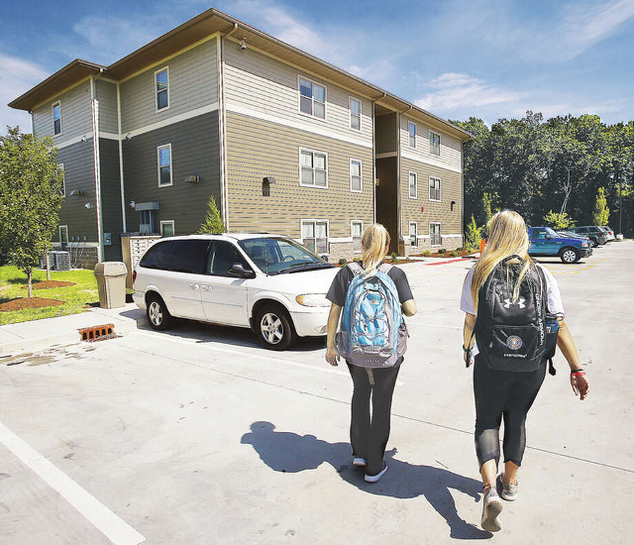 Two Lewis and Clark Community College students walk toward the latest phase of an on campus housing unit at 824 Elm St. in Godfrey Tuesday. The new apartments already have tenants and match an earlier facility next door. The new phase was dedicated Tuesday afternoon.