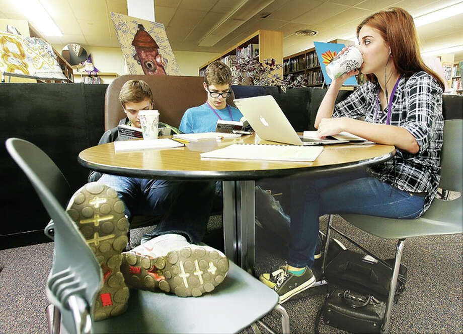Civic Memorial High School students enjoy coffee and the relaxed environment of the new CM Corner Cafe located in a portion of the school library. From the left, school sophmores Logan Haskins, Matthew Cain and Bethanie Simmons study in the new cafe where coffee is just a dollar.