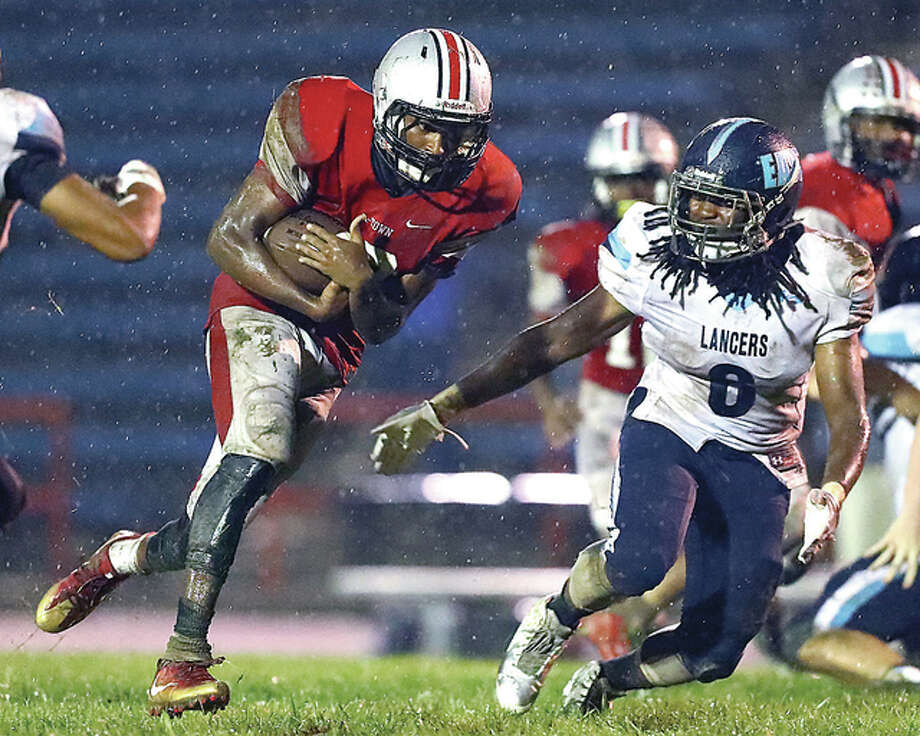 Alton quarterback Taylor Price, left, eludes Belleville East's E.J. Aldridge in Friday night's Southwestern Conference game at Public School Stadium. Photo: Billy Hurst | For The Telegraph