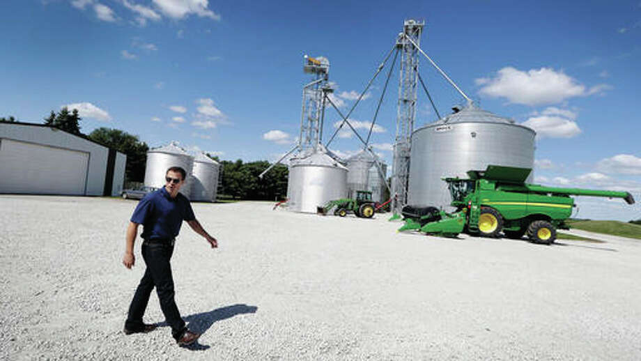 Grant Kimberley walks past grain storage bins and farm equipment on his farm, Friday, Sept. 2, 2016, near Maxwell, Iowa. The men and women who grew what's expected to be the biggest corn crop the United States has ever seen won't benefit from the milestone. Prices are so low that for the third consecutive year, most corn farmers will spend more than they earn. It's a similar story for soybean producers. (AP Photo/Charlie Neibergall) Photo: (AP Photo/Charlie Neibergall)