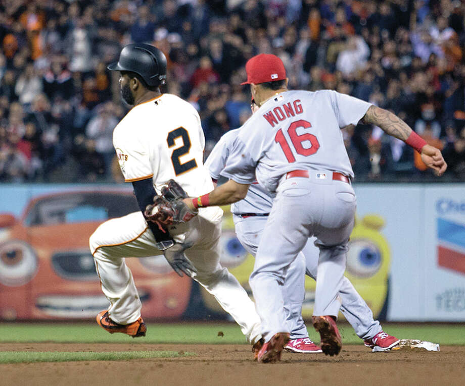 St. Louis Cardinals' Kolten Wong (16) puts the tag on San Francisco Giants' Denard Span, who was caught in a rundown while trying to advance from first to second Jeff Samardzija's sacrifice fly in the fifth inning Saturday in San Francisco. Photo: AP