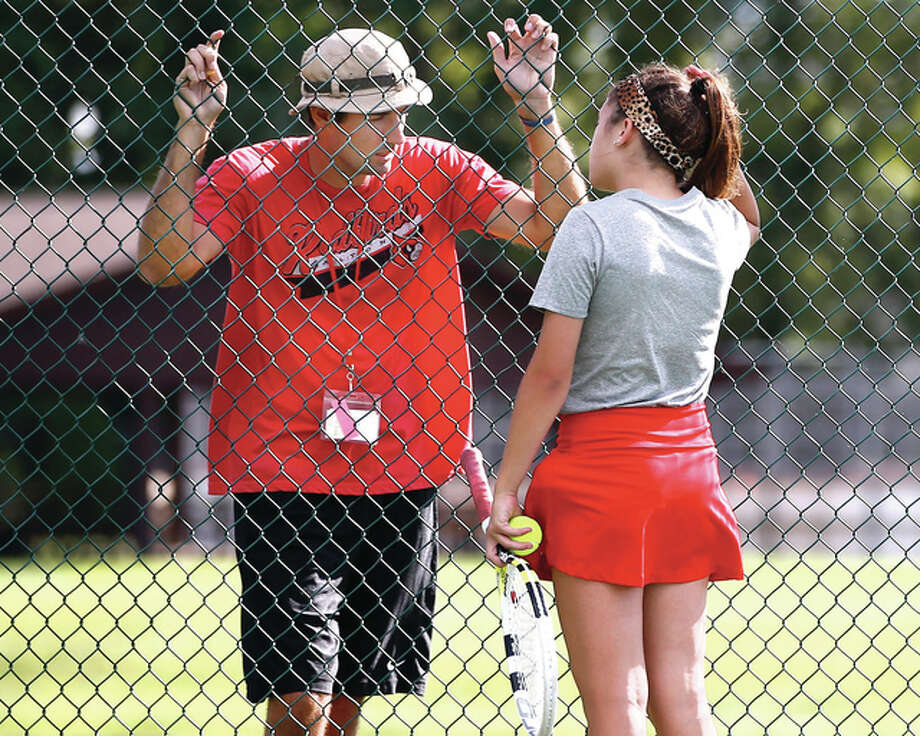 Alton tennis coach Robert Logan (left) talks with Shannon Willis during a match against Metro East Lutheran in Edwardsville on Aug. 26, 2015. Logan lost his fight with cancer on Sunday at age 30. Photo: Billy Hurst / For The Telegraph
