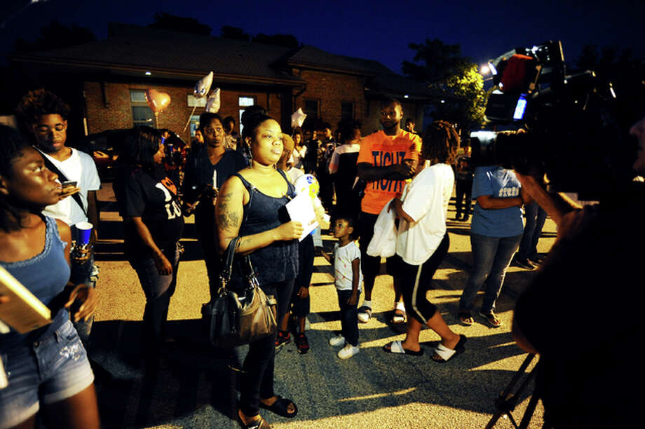 Courtney Hubbard's mother, Jessica Roland, is interviewed by a St. Louis television news station at Sunday night's candlelight vigil for her son.