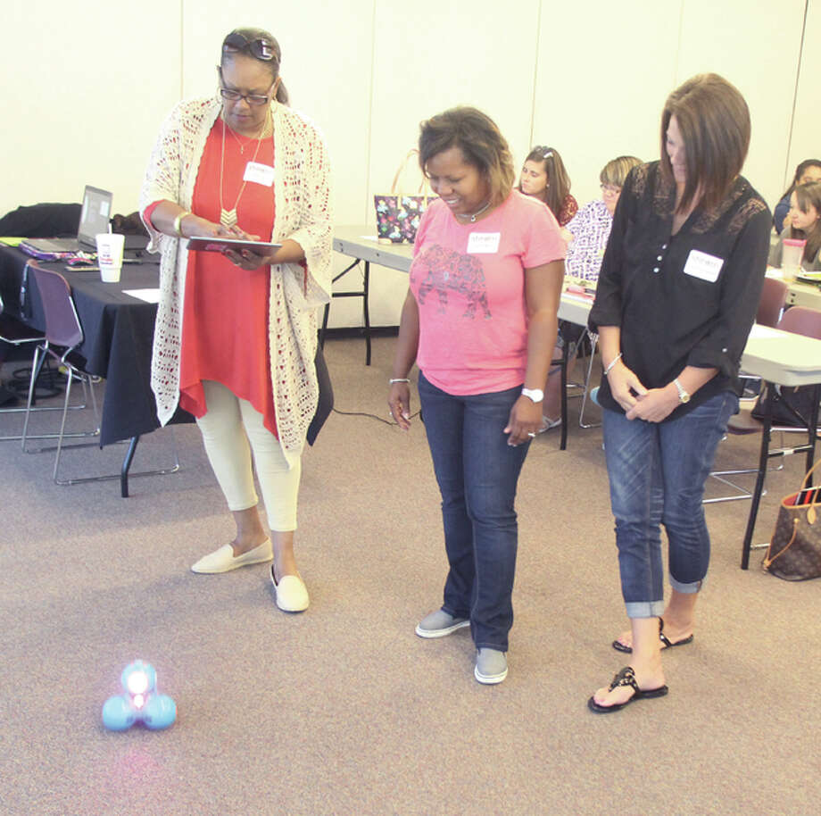Lisa Tate (left), an early childhood educator at SIUE's Early Headstart Program in East St. Louis; Lavicia William, of the East St. Louis School District; and Christine Counton, an educator with Granite City's Early Childhood Center, watch as a small robot travels across the floor Monday at the Early Childhood STEAM (Science, Technology, Engineering Arts and Math) Conference at SIUE. About 190 early childhood educators and SIUE education students participated.