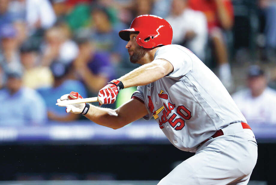 Cardinals' Adam Wainwright follows the flight of his broken-bat single to drive in the fifth inning Tuesday at Denver. The hit drove in two runs off Rockies relief pitcher Eddie Butler. Photo: AP