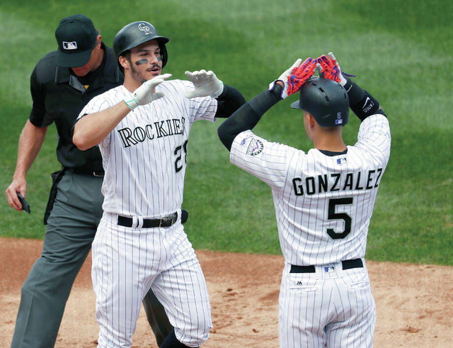 The Rockies' Carlos Gonzalez, right, congratulates Nolan Arenado as he crosses home plate after hitting a grand slam off Cardinals starter Luke Weaver in the second inning Wednesday's game in Denver. Photo: AP