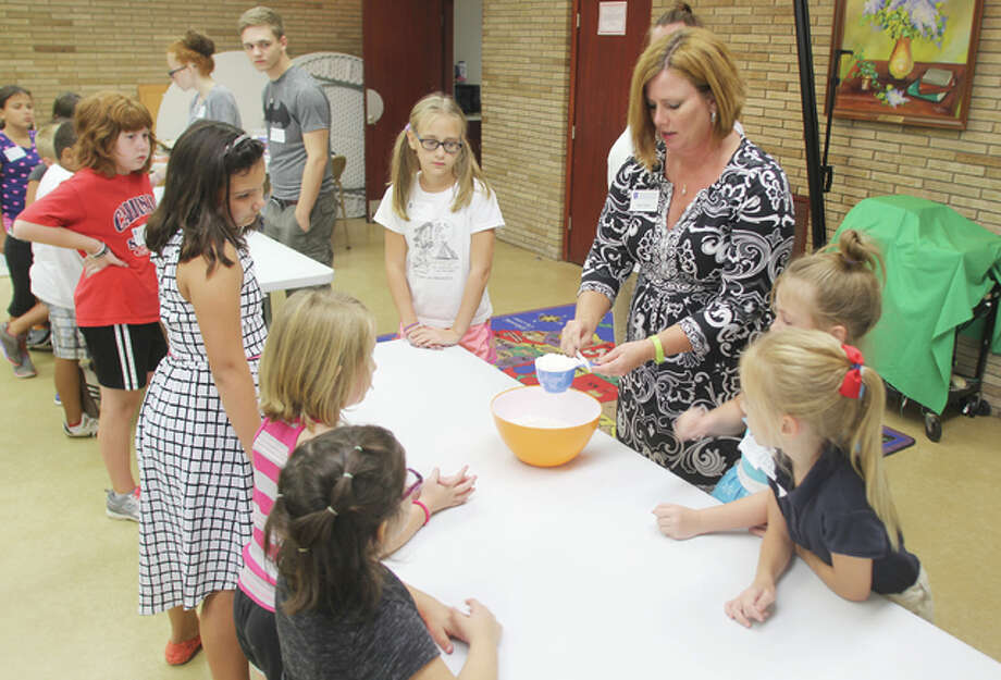 Julie Fulton of the University of Illinois Extension in Collinsville shows children how to prepare pumpkin pancakes Tuesday at the Wood River Public Library. Fulton was teaching a five-week class called Illinois Junior Chefs, which was attended by about a dozen children 6 to 12 years old.