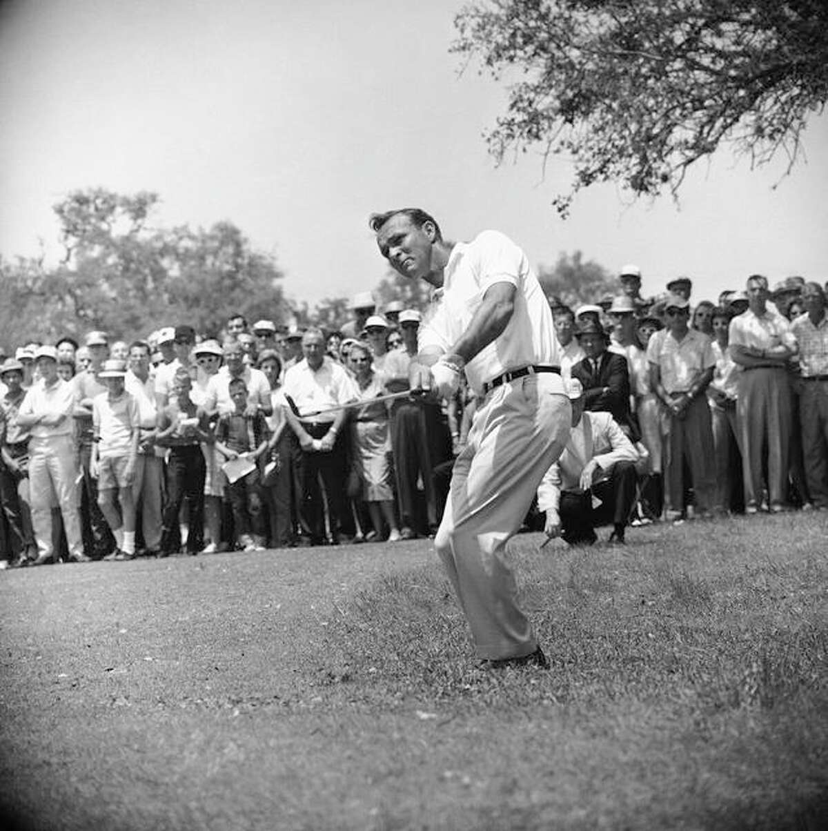 """This April 29, 1962, file photo shows Arnold Palmer, lifting an iron shot from No. 5 fairway in the final round of the Texas Open in San Antonio. Palmer, who made golf popular for the masses with his hard-charging style, incomparable charisma and a personal touch that made him known throughout the golf world as """"The King,"""" died Sunday, Sept. 25, in Pittsburgh. He was 87."""