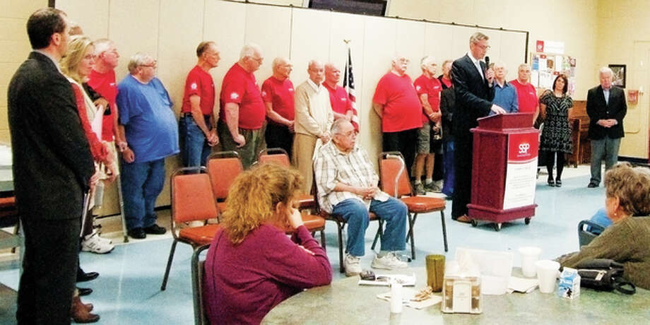 Illinois Treasurer Michael W. Frerichs addresses a crowd at Alton's Senior Services Plus on Thursday. Before Frerichs spoke, Francis Gonzales, seated middle, gave his account of the effects he and his fellow residents of Skyline Towers Apartments in Alton are dealing with because of recent government cuts.