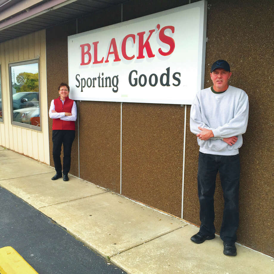 Owner of Black's Sporting Goods Dave Hachting, right, poses with Manager Cheryl McLagan at the Godfrey store, which is celebrating its 60th anniversary this year.