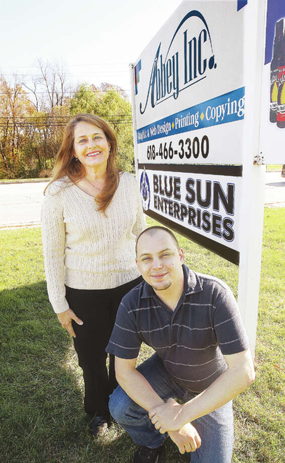 Cherie Schroeder, left, and Chad Springman pose in front of their companies' signs at 3312 Godfrey Road in Godfrey. Springman's business, Blue Sun Enterprises, now leases a space from Schroeder in the Godfrey location.