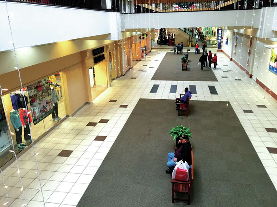 Shoppers browse storefronts at Alton Square Mall on Friday morning. A Macy's spokeswoman said Black Friday traffic this year was about the same as last year.