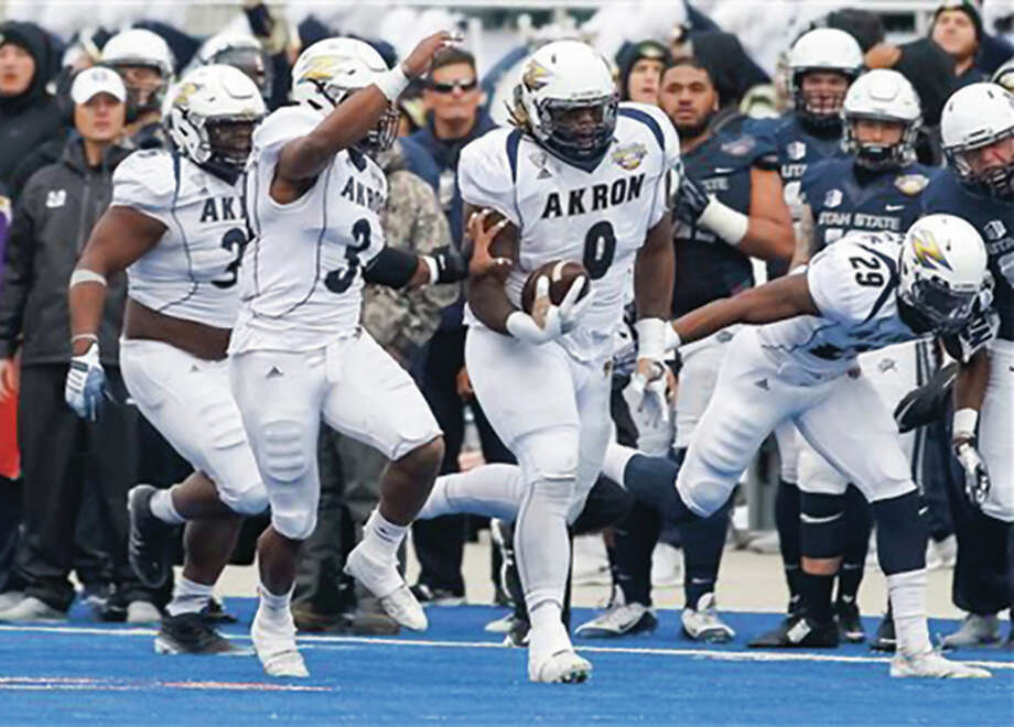 Akron Zips defensive tackle Rodney Coe (middle, right) returns a recovered fumble 56 yards to set up a 29-yard field goal on the final play of the first half in the Zips' 23-21 victory over Utah State in the Famous Idaho Potato Bowl on Tuesday in Boise, Idaho. Coe, a former Telegraph Player of the Year with the Edwardsville Tigers, ended his college career with the bowl victory. Coe was the top-ranked running back prospect in Illinois in 2010 as a 6-foot-3, 238-pound senior at Edwardsville. Coe committed to Iowa out of high school, but spent two seasons at Iowa Western Community College before playing his junior season at Iowa State. After taking a redshirt season as a transfer in 2014, the 305-pound Coe helped Akron to an 8-5 record and its first FBS bowl win as a senior. Photo: Associated Press