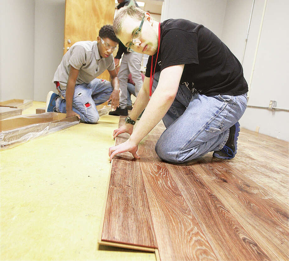 """Alton High School construction students lay down a laminate flooring Thursday in the """"Guardian Angel Pantry"""" at the Catholic Charities building, 3512 McArthur Blvd. in Alton."""