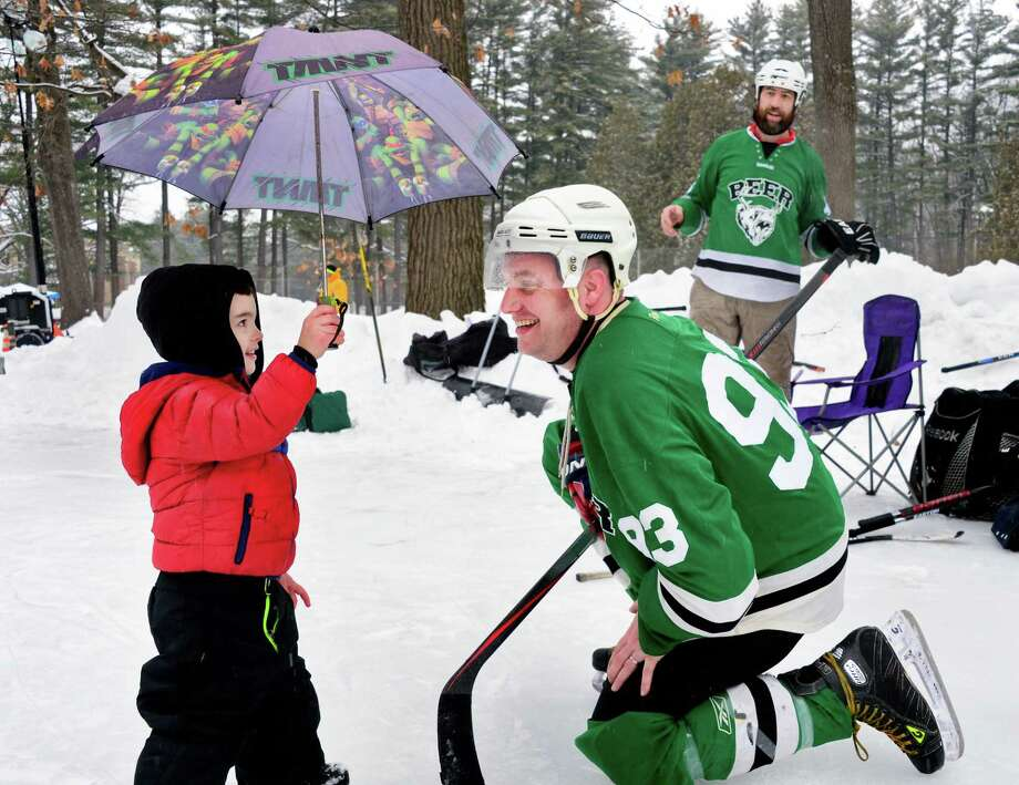 Two-year-old Cameron Clingo offers the shelter of his umbrella to his father Justin Clingo of Long Island as a light rain falls on the Saratoga Frozen Springs Classic - Pond Hockey Tournament at Saratoga Spa State Park Saturday Feb. 10, 2018 in Saratoga Springs, NY.  (John Carl D'Annibale/Times Union) Photo: John Carl D'Annibale, Albany Times Union / 20042846A