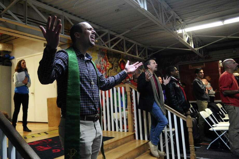 Pastor David Borden, center left, holds his hands out in prayer while singing during the Stanwich Congregational Church service inside Revolution Fitness on Pacific Street in Stamford on Jan. 14. Photo: Michael Cummo / Hearst Connecticut Media / Stamford Advocate