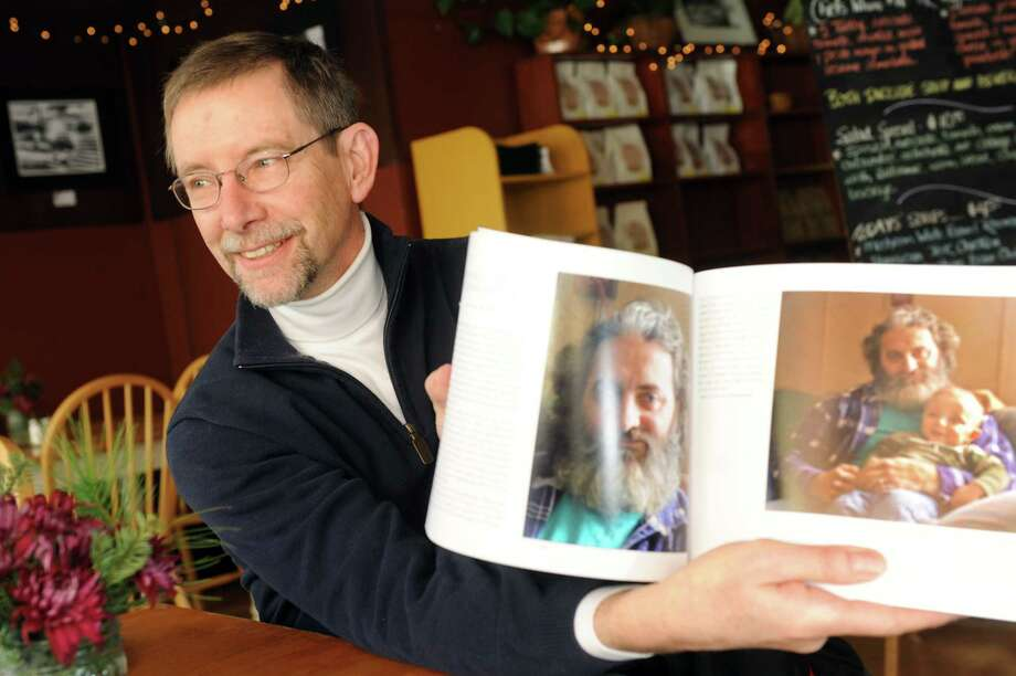 "Dr. Daniel Way shows a picture from his book ""Never a Dull Moment"" on Wednesday, Jan. 8, 2014, at the Rock Hill Bakehouse in Glens Falls, N.Y. Way is a North Country doctor, photographer and writer. (Cindy Schultz / Times Union) Photo: Cindy Schultz / 00025257A"