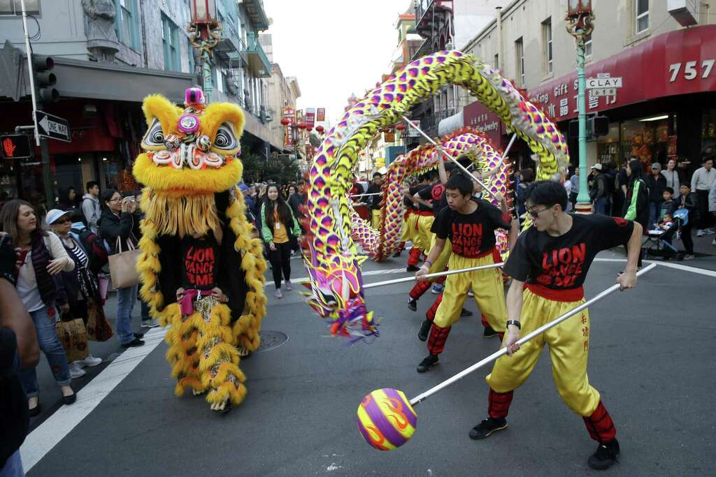 a lion and a dragon perform in a parade at the chinese new year flower market - San Francisco Chinese New Year