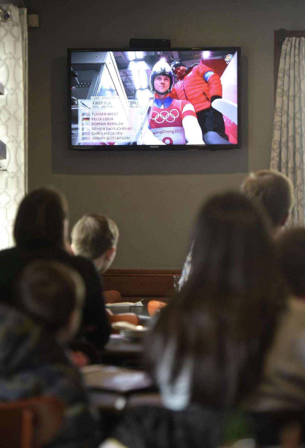 Diners watch Ridgefield Olympian Tucker West compete in the men's luge at the 2018 PyeongChang Olympic Games, South Korea, at the Tigers Den Sports Bar and Grill in Ridgefield, Conn, on Saturday, February 10, 2018.