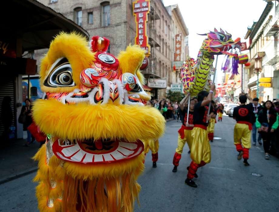 A lion and a dragon perform in a parade on Grant Avenue at the Chinese New Year Flower Market Fair in San Francisco, Calif. on Saturday, Feb. 10, 2018. The weekend festival in Chinatown kicks off events celebrating the Year of the Dog. Photo: Paul Chinn, The Chronicle