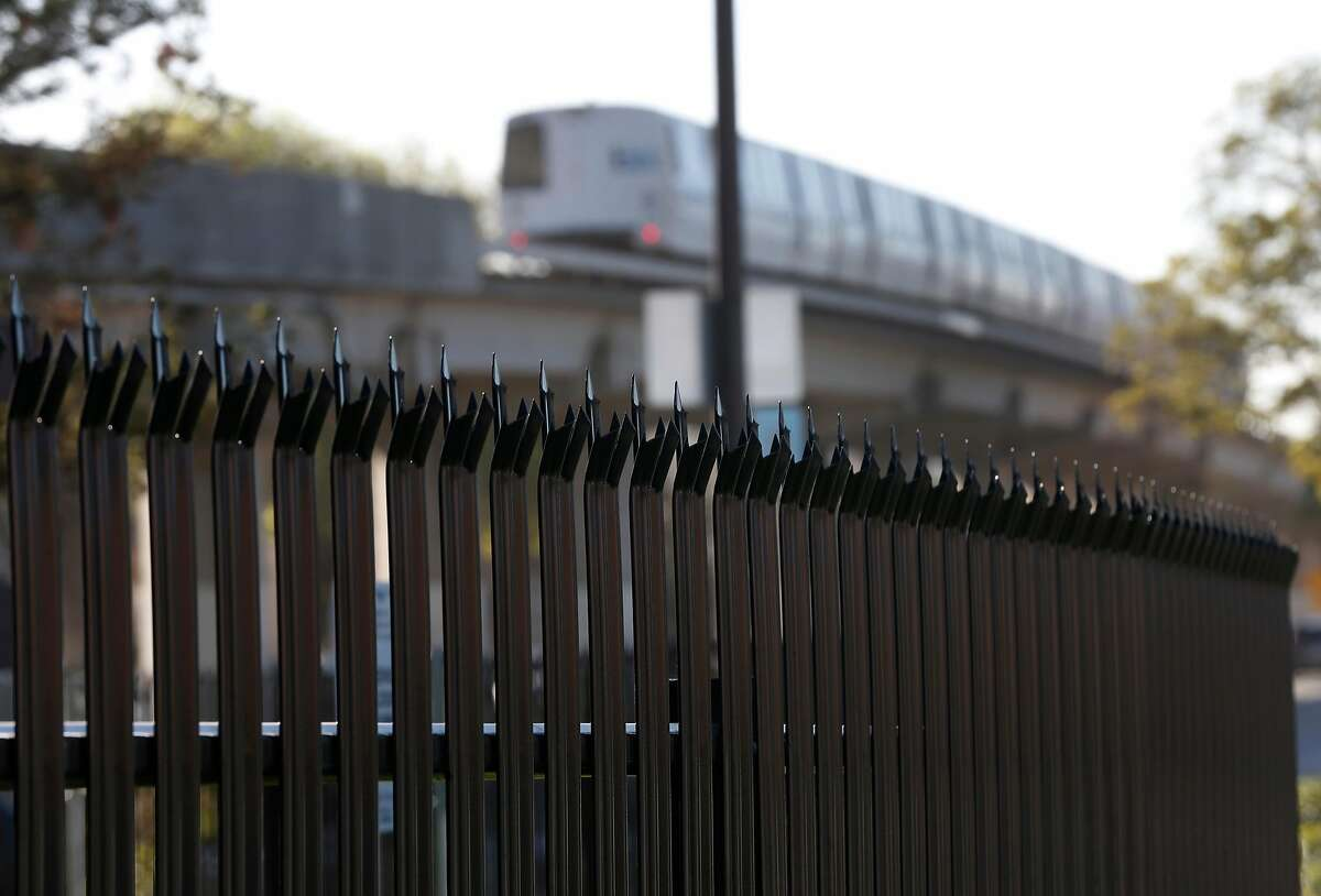A southbound BART train en route to the Warm Springs station rolls past a spiked steel fence erected at the site of a former homeless encampment next to the tracks at Martin Luther King Jr. Boulevard and 63rd Street in Berkeley, Calif. on Saturday, Feb. 10, 2018. BART installed the fence to prevent the campers from returning but the prison-like fence has angered a Berkeley city council member and many residents.