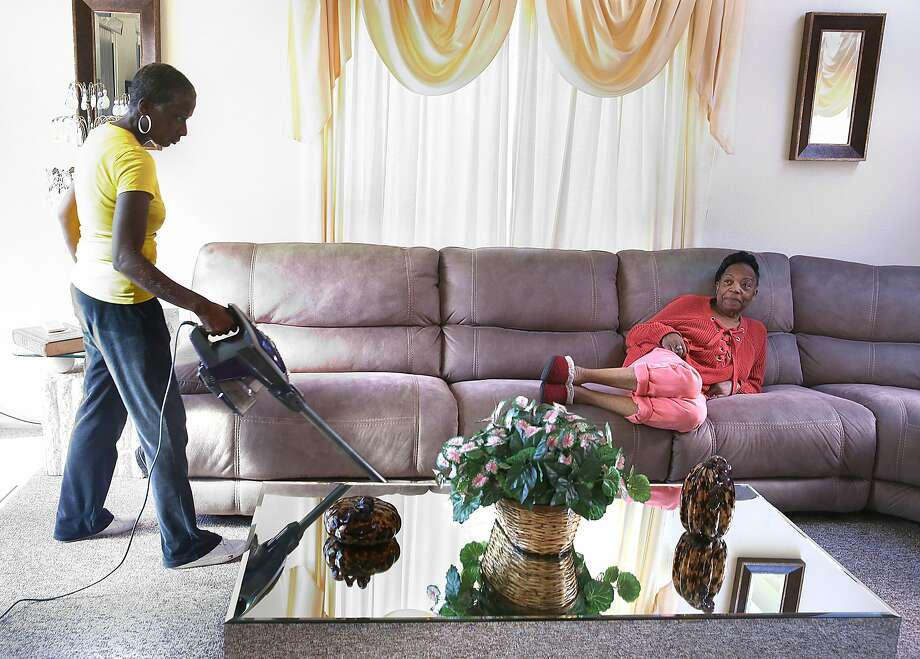 Support at Home worker Sonia Wright vacuums and chats with client Margie Cherry in S.F. Photo: Liz Hafalia, The Chronicle