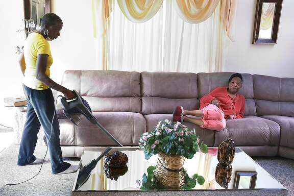 Margie Cherry (right) talks with her home health care provider Sonia Wright (left) as she vacuums the floor at home on Friday, February 9, 2018, in San Francisco, Ca.