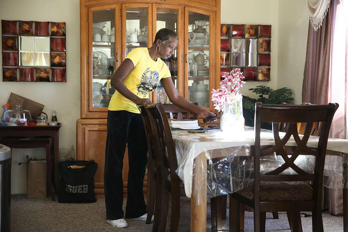 Home health care provider Sonia Wright organizes the table at the home of Johnny and Margie Cherry on Friday, February 9, 2018, in San Francisco, Ca.