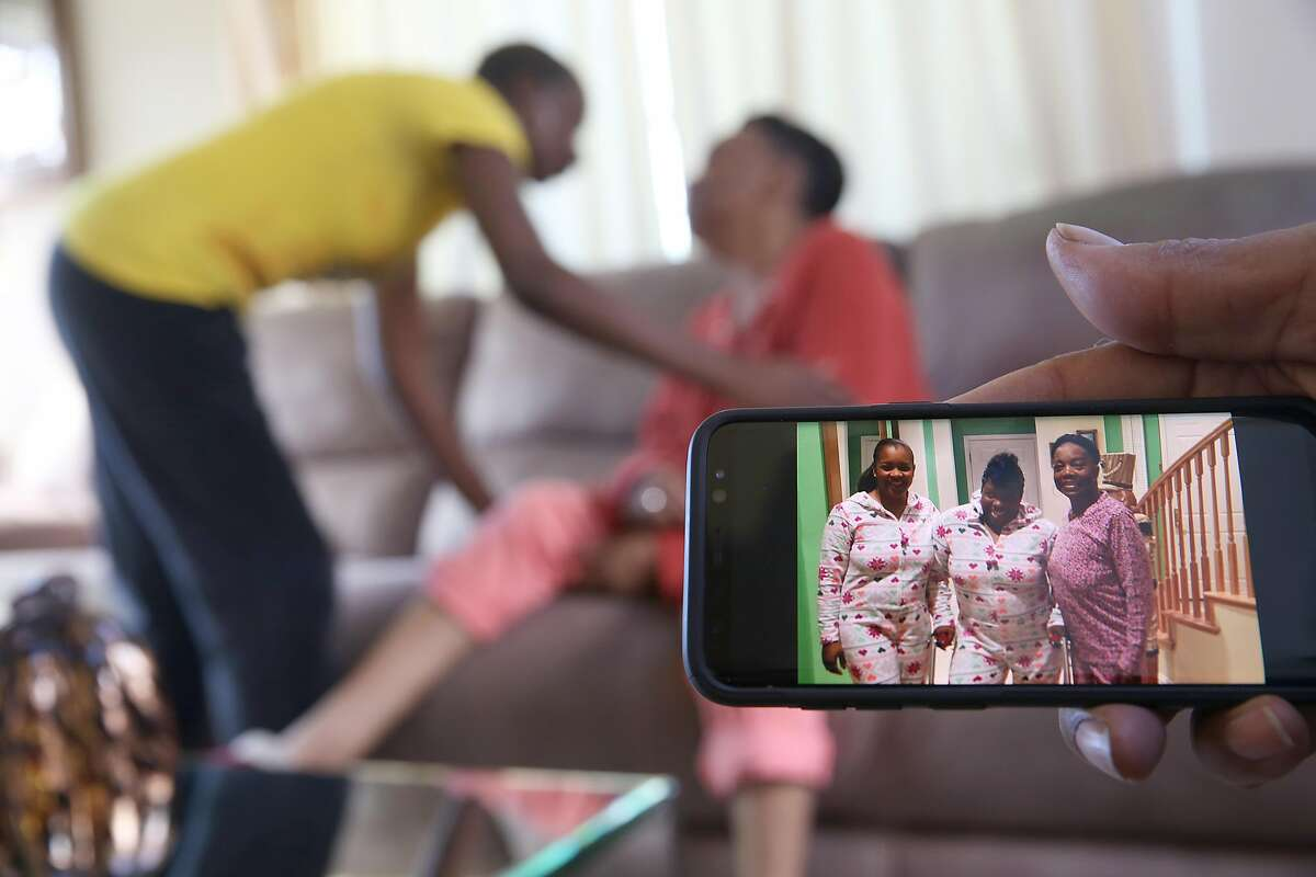 Home health care provider Sonia Wright (left in background) says goodbye to Margie Cherry (middle in background) as her husband Johnny Cherry (right) shows pictures of Margie (wearing pink) with their two grown daughters at left on phone at home on Friday, February 9, 2018, in San Francisco, Ca.