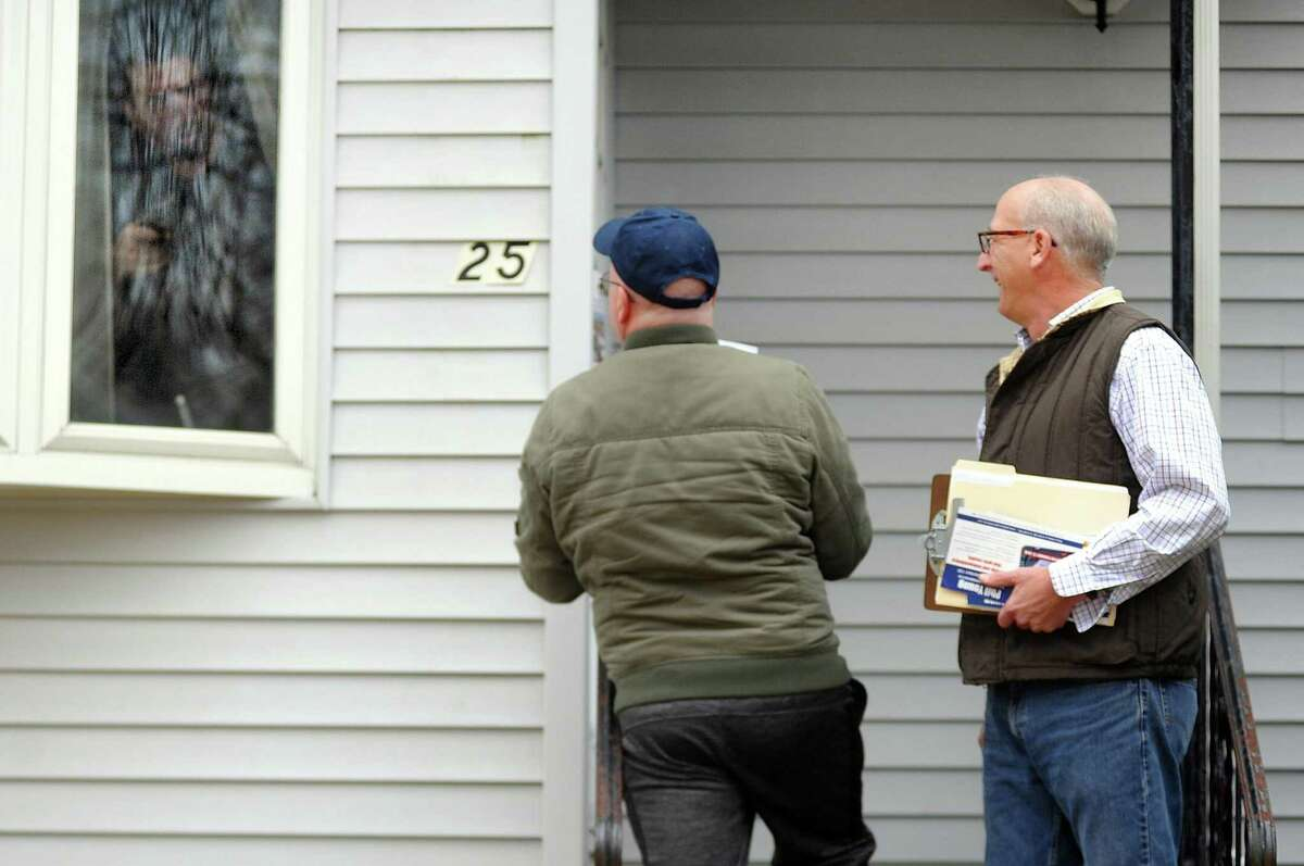 A homeowner holds a handgun as Democratic state representative candidate Phil Young, right, and state rep Joe Gresko go door to door in Stratford, Conn. on Saturday Nov. 10, 2018. Young is running for the seat being vacated by Stratford Mayor Laura Hoydick. The special election is on Feb. 27th.