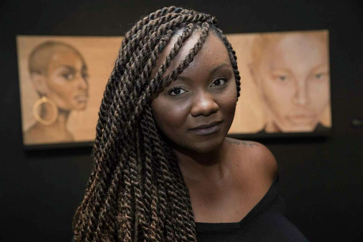 Artist Aesha Lee poses with her portraits at her