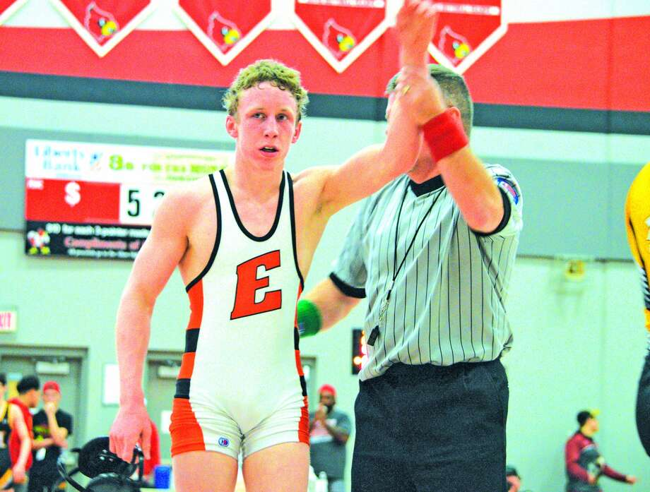 Edwardsville sophomore Luke Odom left, has his hand raised by the referee to signify his victory over Carlos Champagne of Chicago Heights Marian on Saturday in the championship match of the Class 3A Alton Sectional.