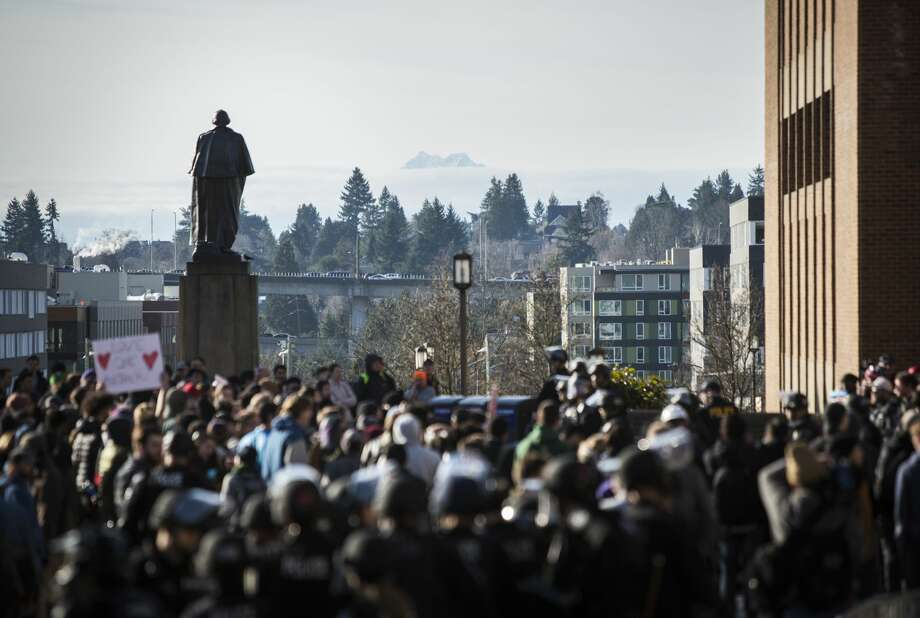 "A statue of George Washington looms over a group of Seattle police and counterprotesters during a ""Freedom Rally"" with the school's College Republicans group at Red Square on the University of Washington campus, Saturday, Feb. 10, 2018 in Seattle. Several arrests were made during the rally and counterprotest, despite barriers meant to separate the two groups. Photo: Lindsey Wasson"