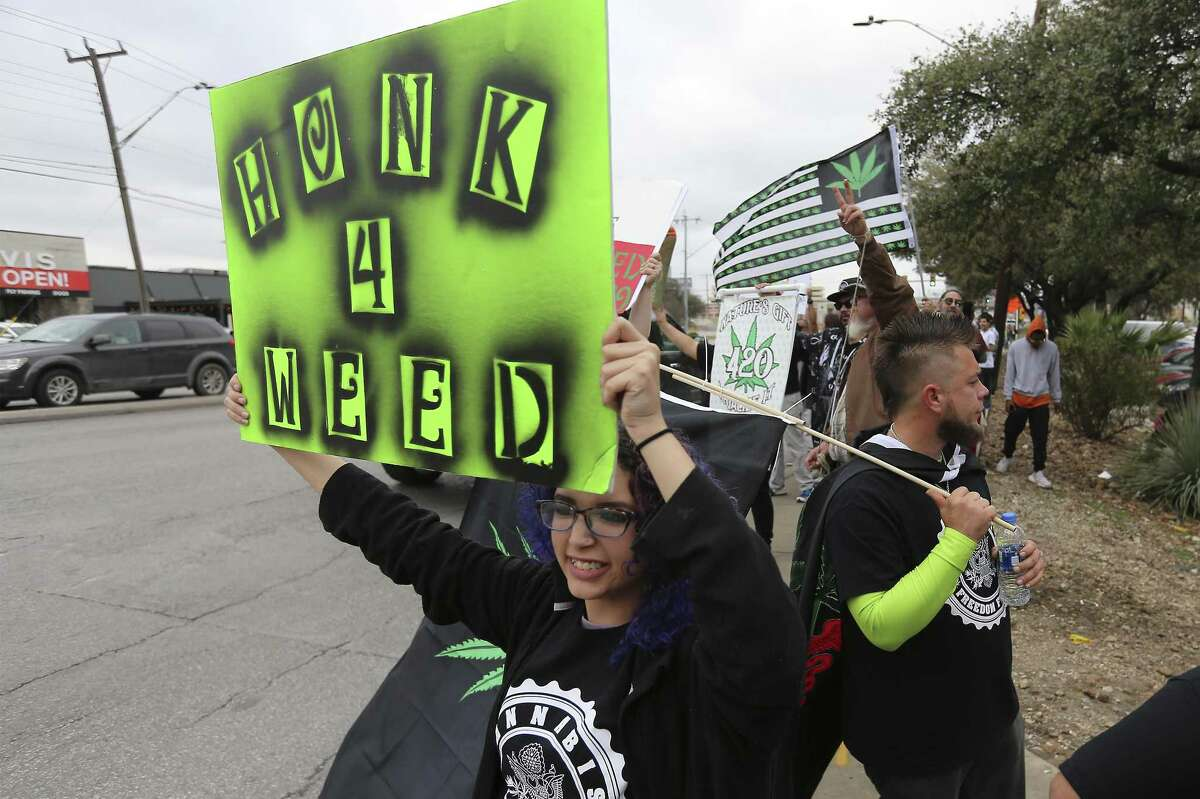 Arianna Casillas (foreground) joins a crowd in favor of the legalization of cannabis in Texas gathered to rally at the intersection of San Pedro and Rector on Saturday, Feb. 10, 2018. The organization 420OpenCarry held the event to support the open use of recreational marijuana. (Kin Man Hui/San Antonio Express-News)
