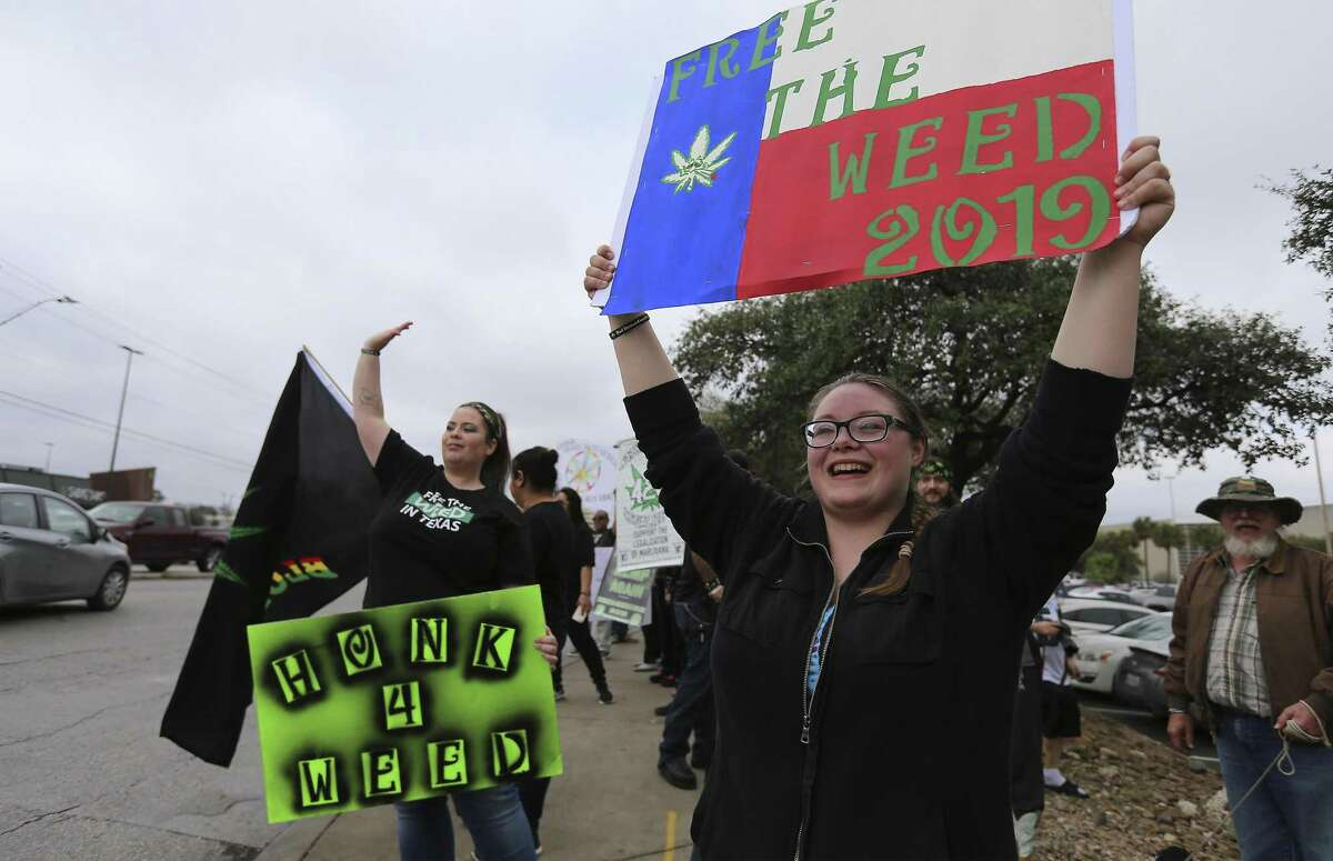 Dani Traeger (right) joins a crowd in favor of the legalization of cannabis in Texas gathered to rally at the intersection of San Pedro and Rector on Saturday, Feb. 10, 2018. The organization 420OpenCarry held the event to support the open use of recreational marijuana. (Kin Man Hui/San Antonio Express-News)