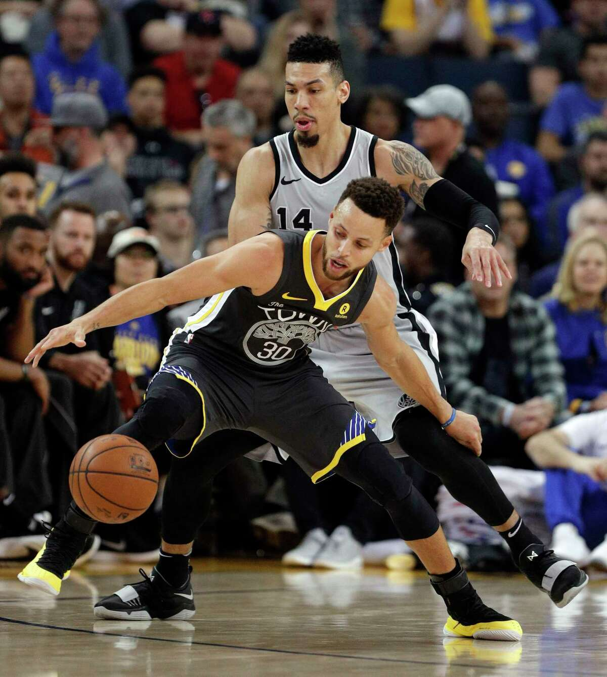 Stephen Curry (30) loses control of the ball while defended by Danny Green (14) in the first half as the Golden State Warriors played the San Antonio Spurs at Oracle Arena in Oakland, Calif., on Saturday, February 10, 2018.