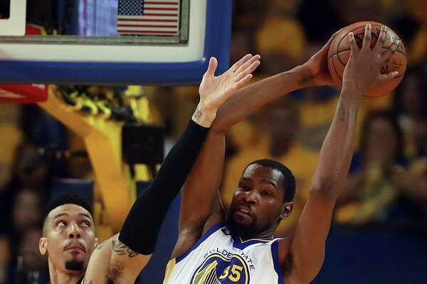 Golden State Warriors' David West, left, and San Antonio Spurs' Danny Green reach for the ball during the first half of an NBA basketball game Saturday, Feb. 10, 2018, in Oakland, Calif. (AP Photo/Ben Margot)