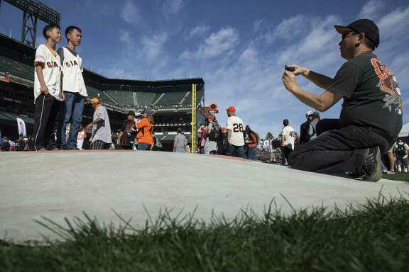 A man takes photos of his two children on the pitcher's mound as families take the field during the Giants' FanFest festivities at AT&T Park on Saturday in San Francisco.