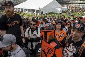 Robert Samson, center, of Benicia dresses as a San Francisco Giants-themed Star Wars character Boba Fett during San Francisco Giants FanFest at AT&T Park Saturday, Feb. 10, 2018  in San Francisco, Calif.