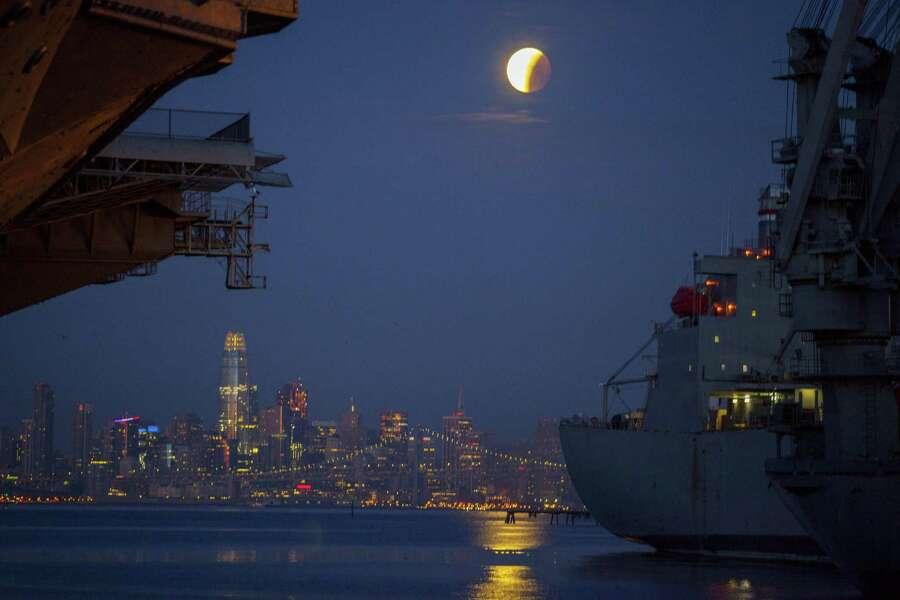 A super blue blood moon lunar eclipse sets over San Francisco as seen from the pier under the aircraft carrier USS Hornet (left) in Alameda on Wednesday, January 31, 2018. Photo: Peter DaSilva / Peter DaSilva / ©2018Peter DaSilva