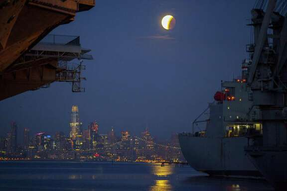 A super blue blood moon lunar eclipse sets over San Francisco as seen from the pier under the aircraft carrier USS Hornet (left) in Alameda on Wednesday, January 31, 2018.